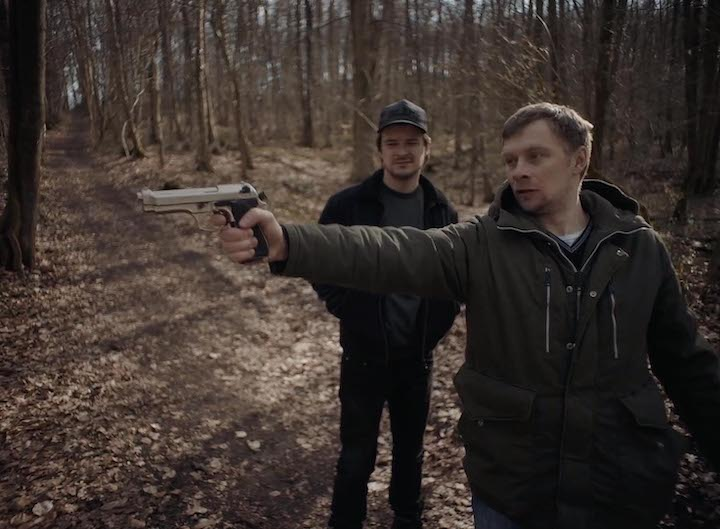Oleg holding a gun in the forest, Andrzej on the background