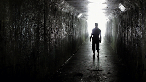 A character standing inside a tunnel, backlit