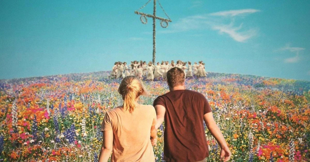 A couple in a field of flowers, against a blue sky, the may pole ahead of them